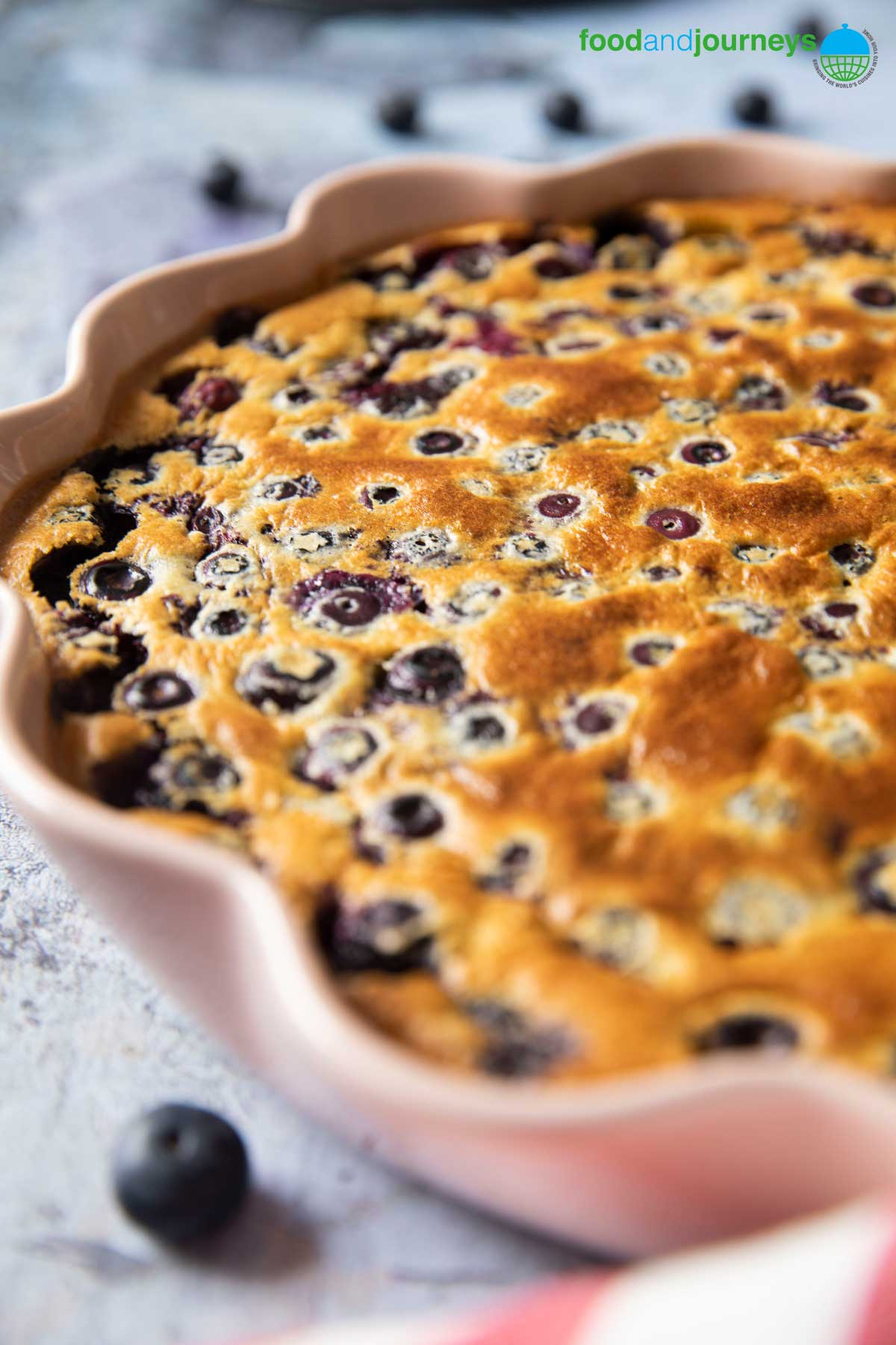 A closer shot of the top of a Basic Clafoutis, highlighting the blueberries in there and the golden top of the custard.