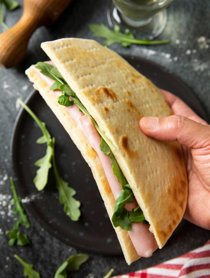 A sandwich made of Italian flatbread, mortadella and some rucola, served with a glass of white wine, ready to be savoured.