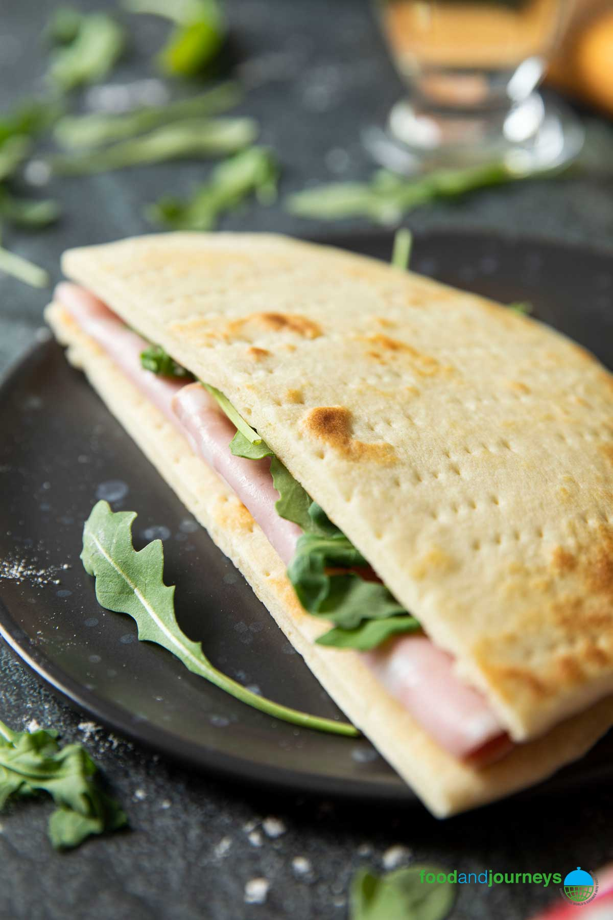 A closer shot of a sandwich made of flatbread cut into halves, with slices of mortadella and some rucola.