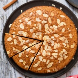 An overhead shot of a cooled Portuguese Honey Cake, with two slices ready for serving, with some sliced almonds on the side.