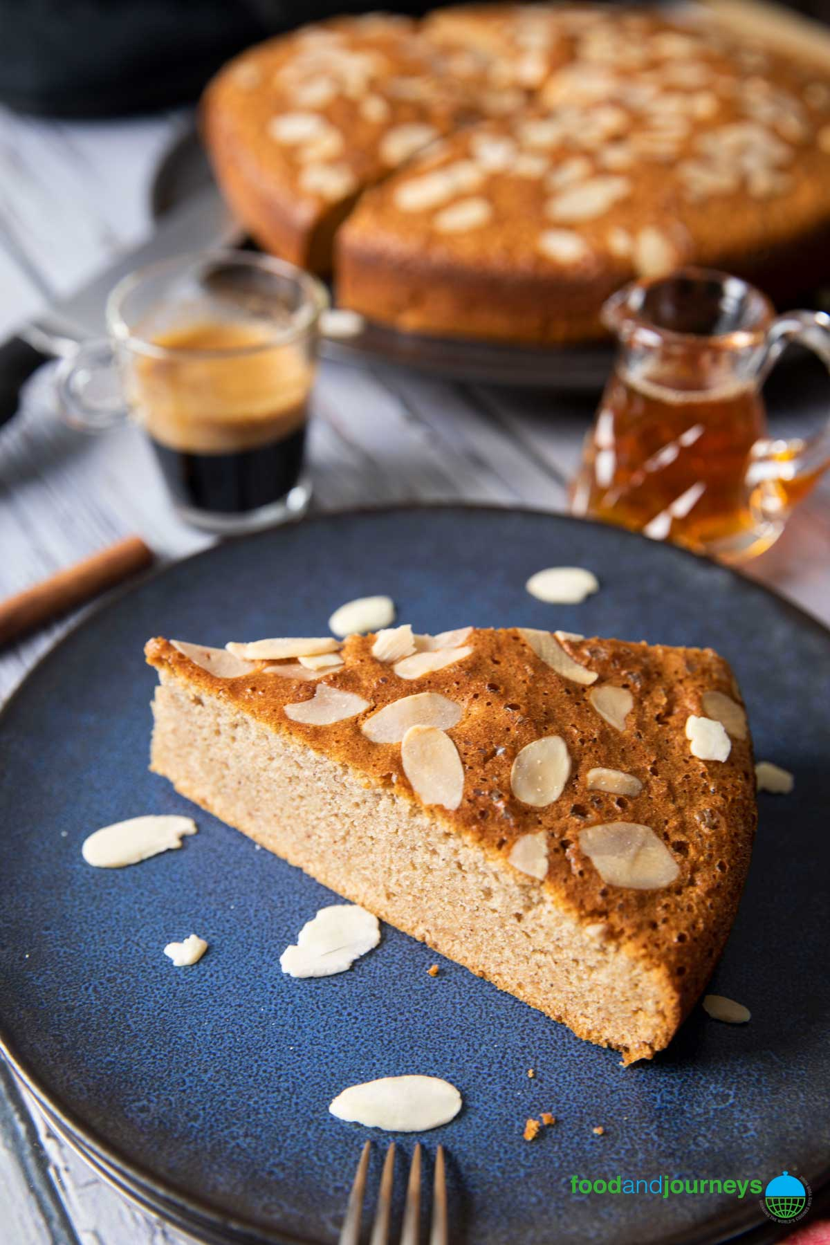 An angled shot of a slice of Portuguese Honey Cake, served with a shot of espresso and sprinkled with more sliced almonds.