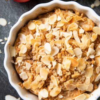 An overhead image of a freshly baked Swedish Apple Crumble, topped with slices of almonds, with fresh apples on the side.
