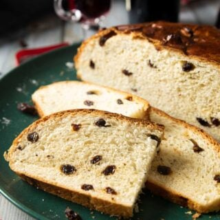 Slices of Christmas Bread on a plate, ready for serving, with some mulled wine on the background.
