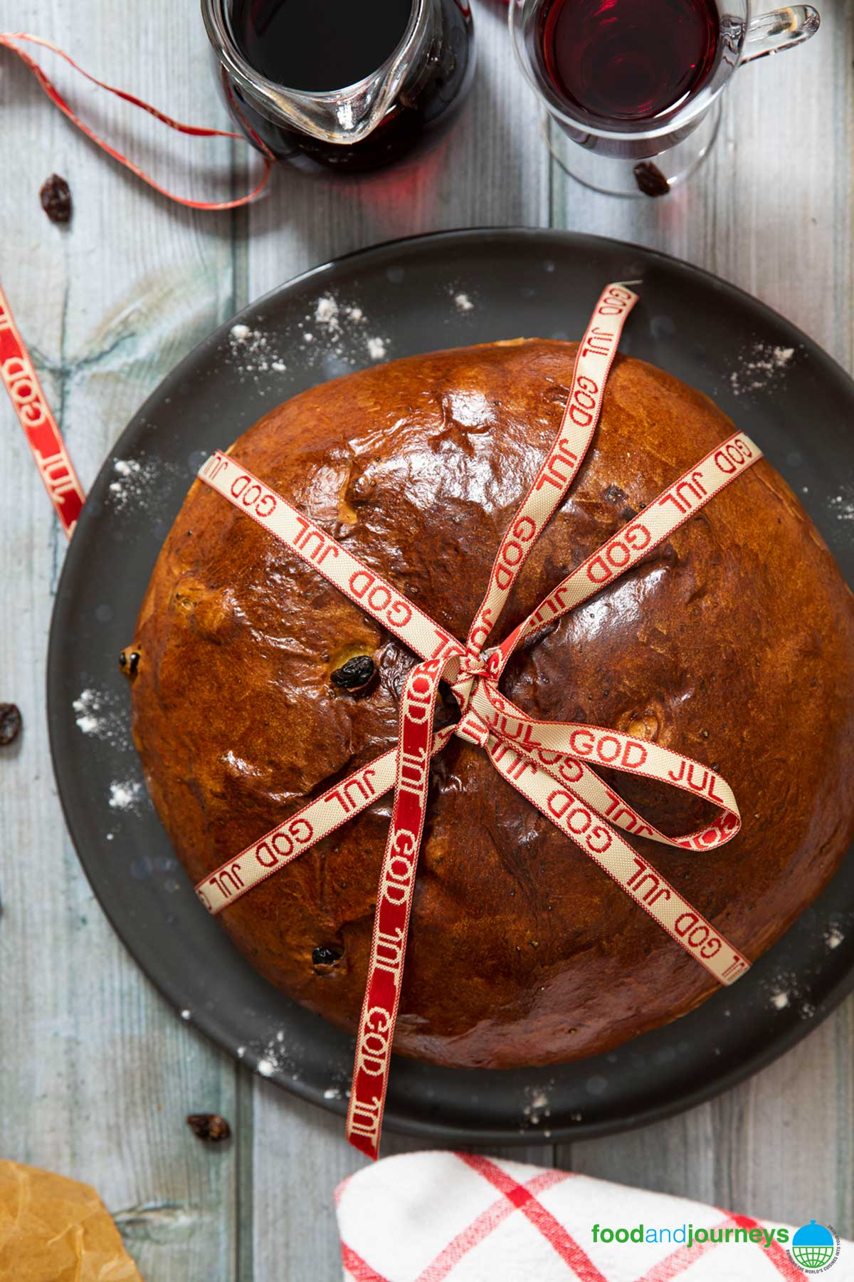 An overhead shot of a freshly baked Norwegian Christmas Cake, with a christmas ribbon tied around it, ready for gifting.
