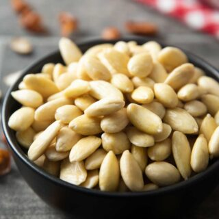 A shot of a bowl of blanched almonds, with peels around it.