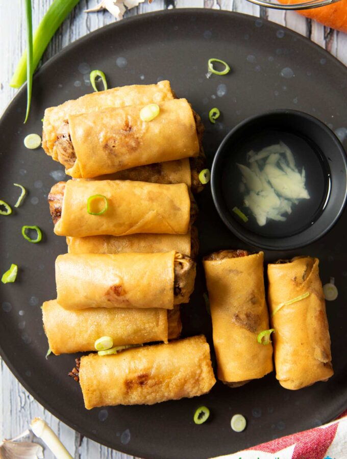 An overhead shot of a plate of Vegetable Spring Rolls, served with vinegar and garlic dipping sauce.