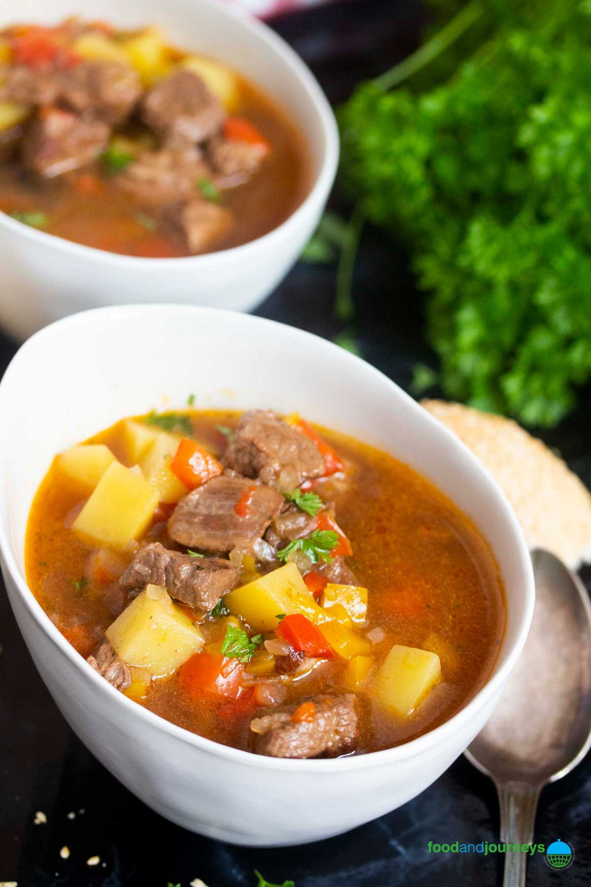 Two bowls of German Goulash Soup, ready for serving, with a slice of bread on the side.
