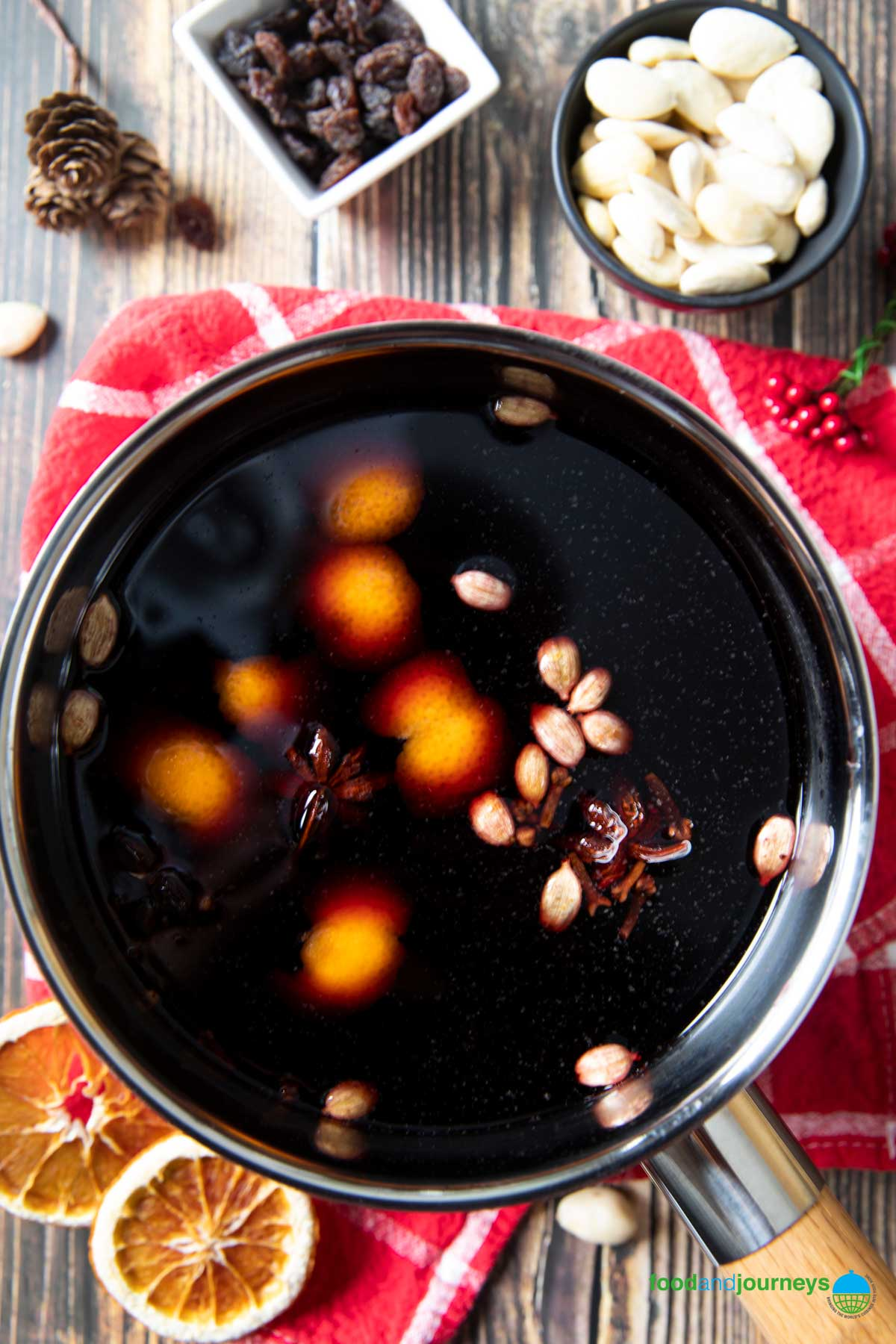An overhead shot of a pan of homemade glögg, ready for serving, with raisins and almonds on the side.