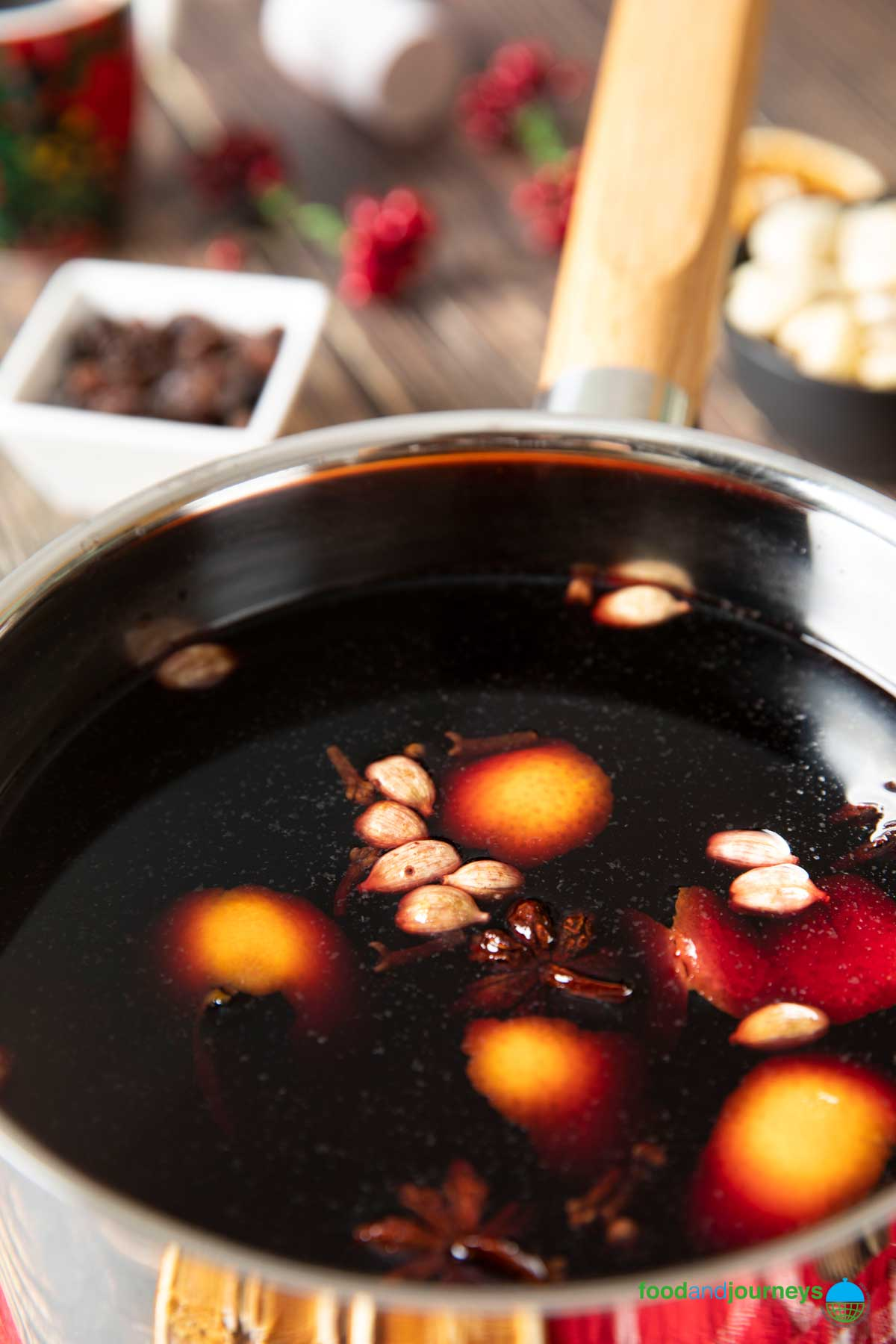 A closer shot of a saucepan filled with Swedish mulled wine, with t he spices floating; on the side, raisins and blanched almonds are shown.
