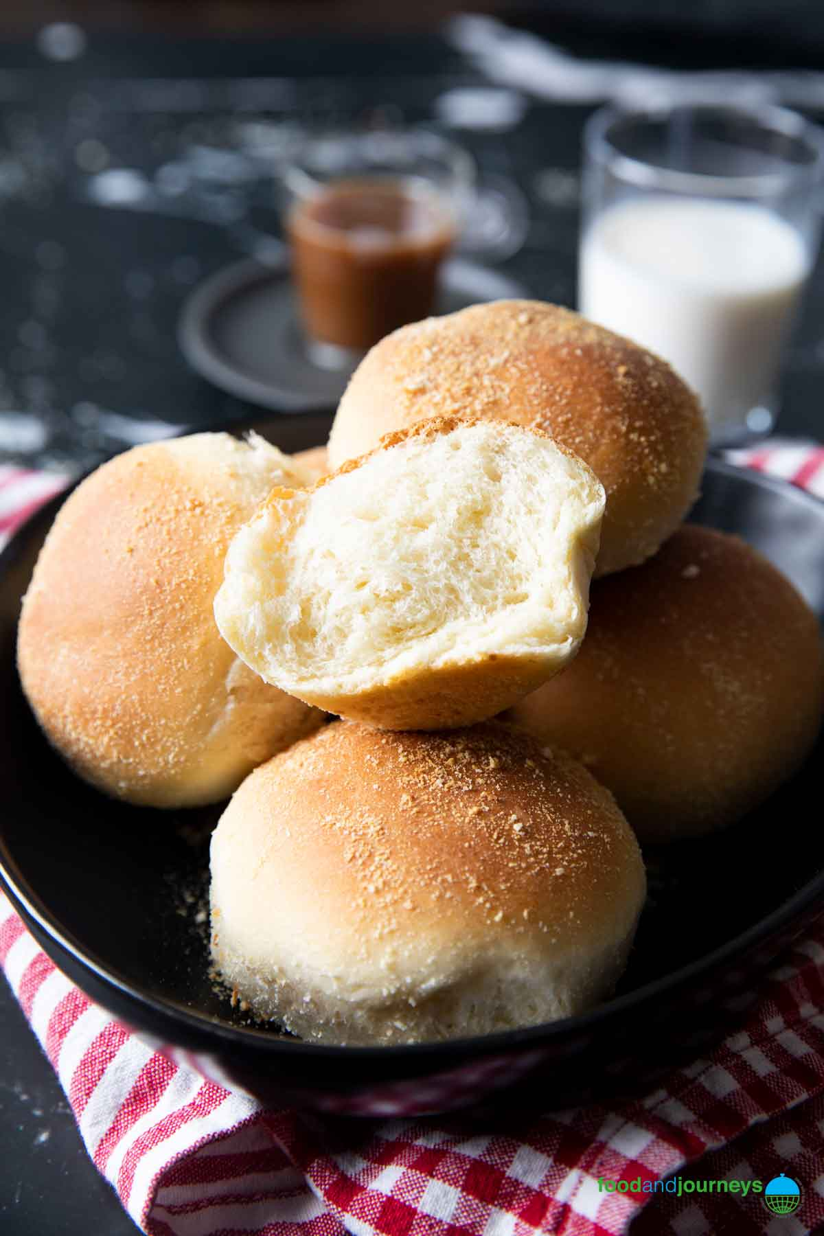 A closer shot of a plate of pandesal, highlighting the soft texture inside the bread roll.
