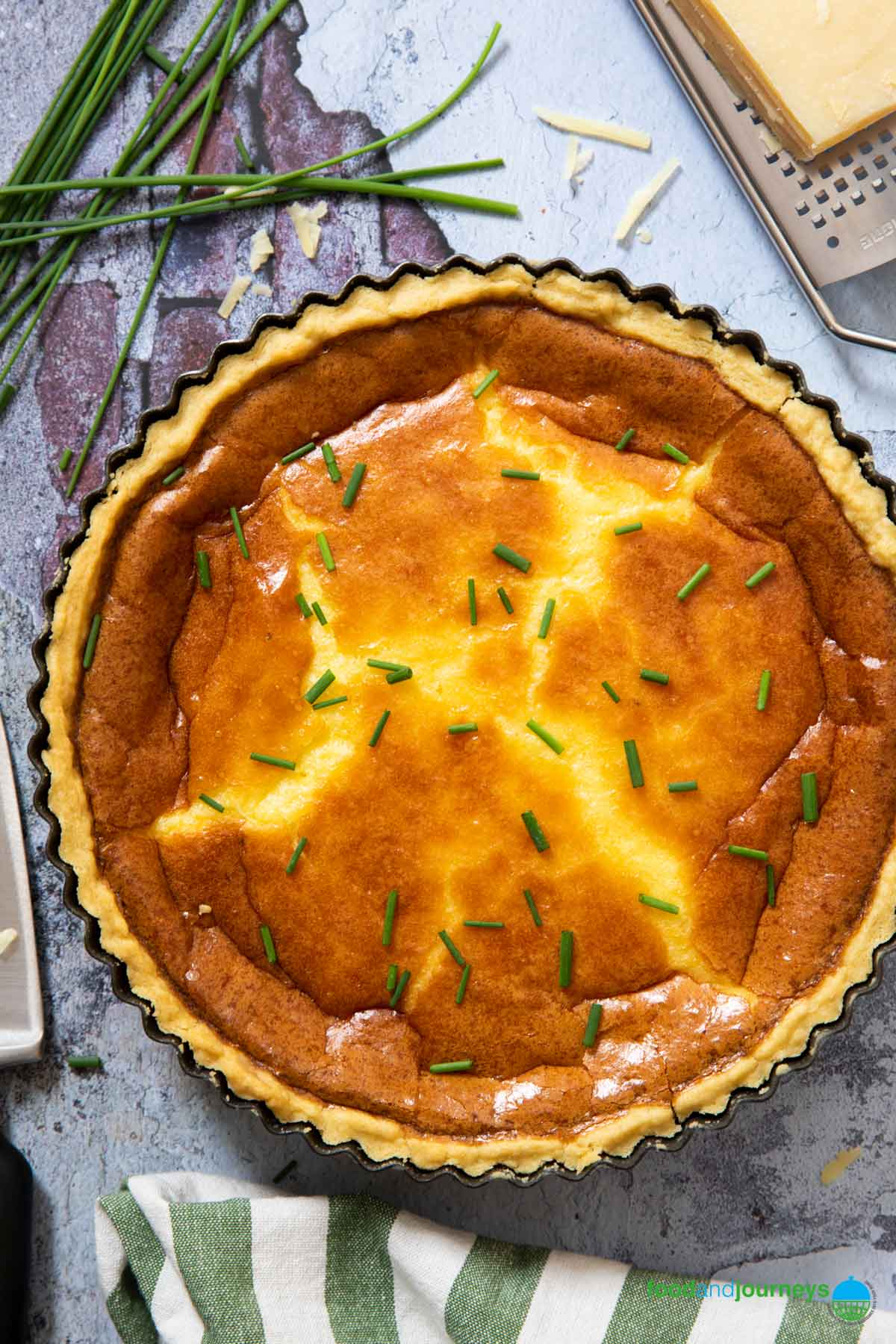An overhead shot of a newly baked Swedish Cheese Pie, with grated cheese on the side.
