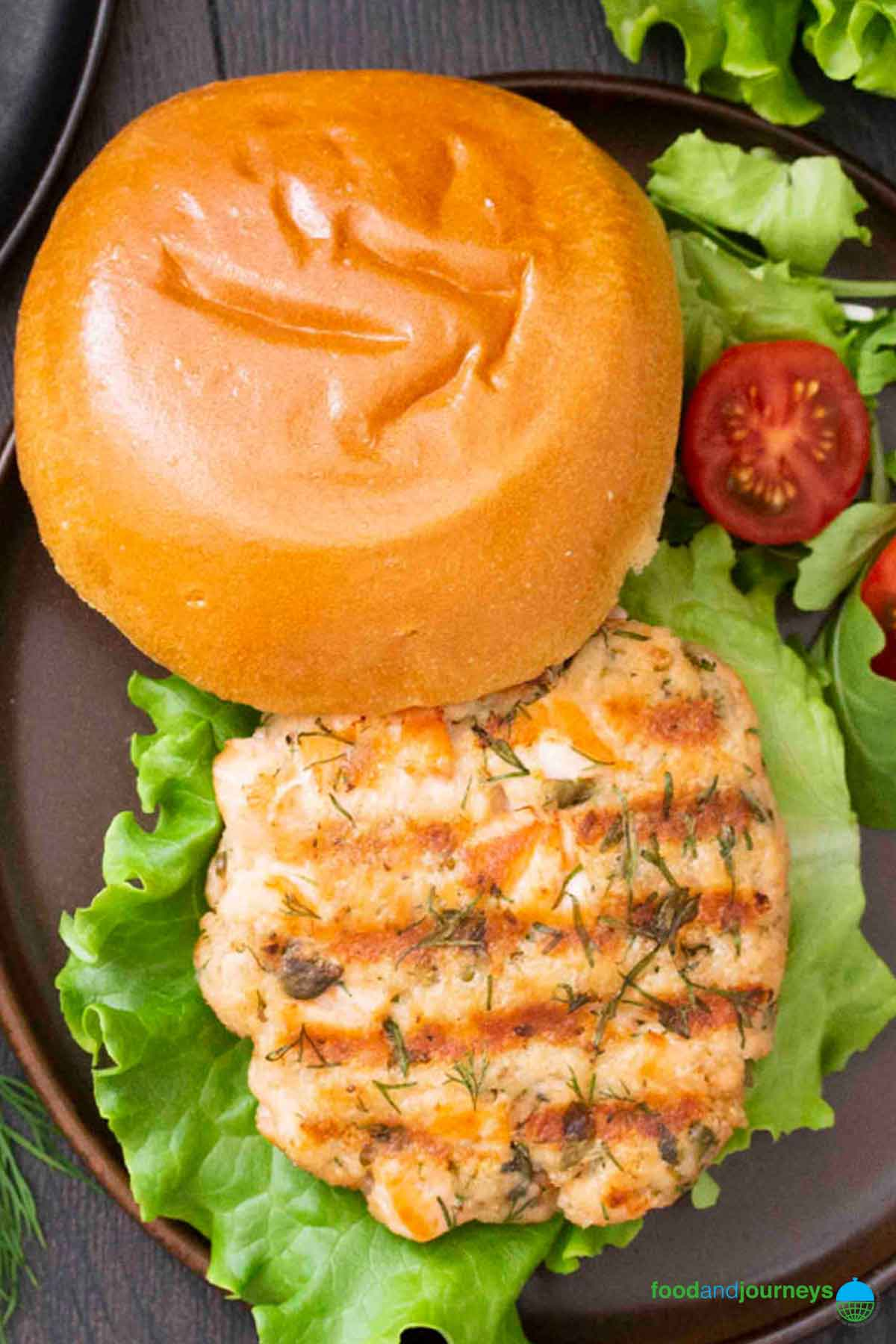 An overhead shot of Swedish Salmon Burger, served with some lettuce and cherry tomatoes.