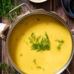 An overhead shot of Creamy Celeriac Soup, garnished with dill, ready for serving.