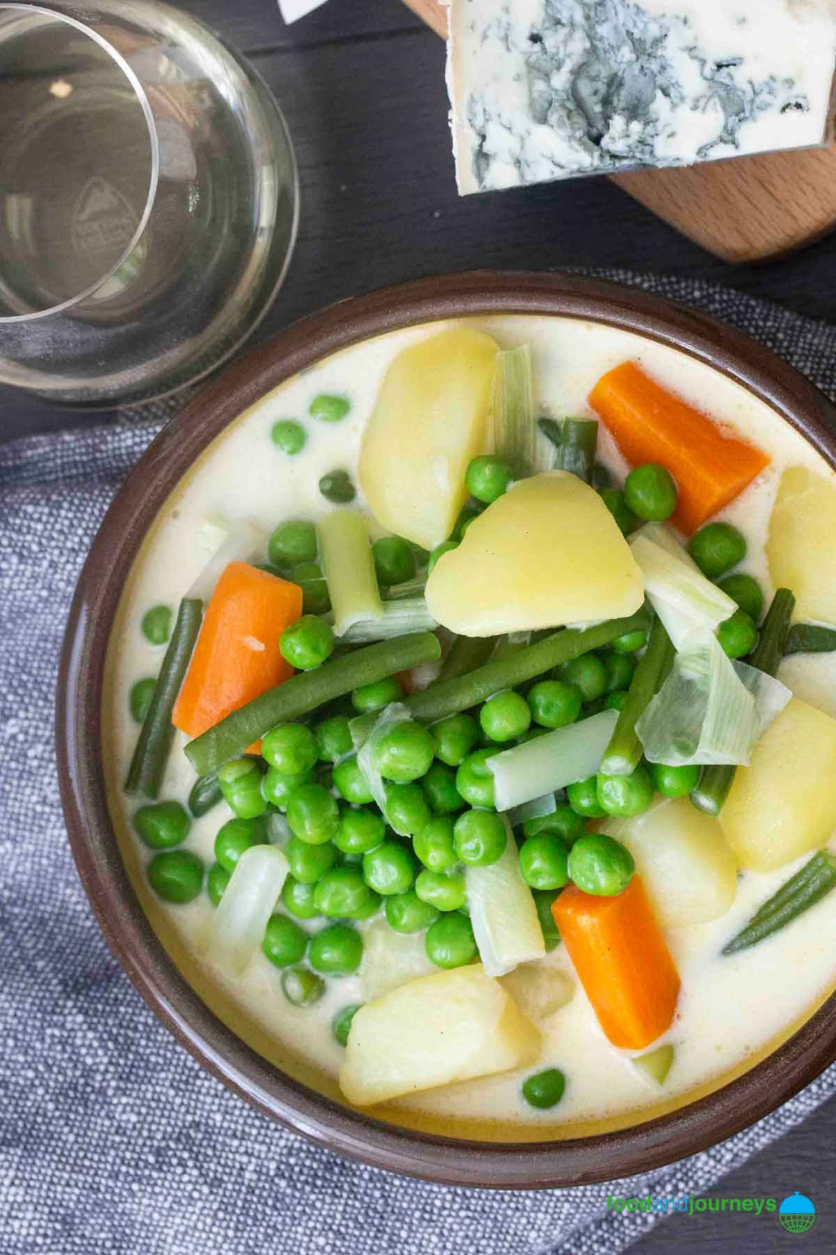 A bowl of Summer Vegetable Soup, served with some blue cheese, and a glass of white wine.