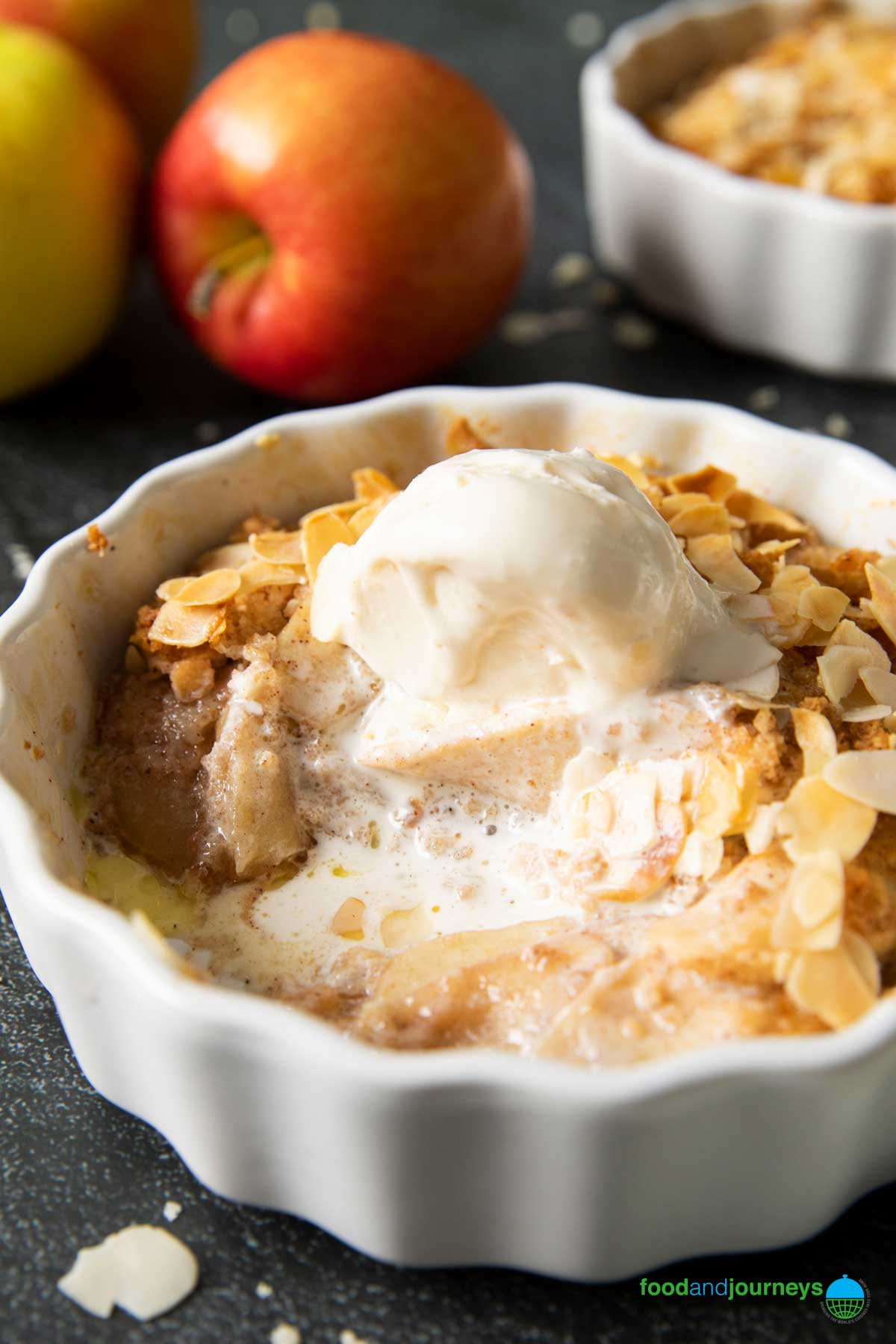 A serving of Apple Crumble, with melted ice cream on top; with some apples on the background.
