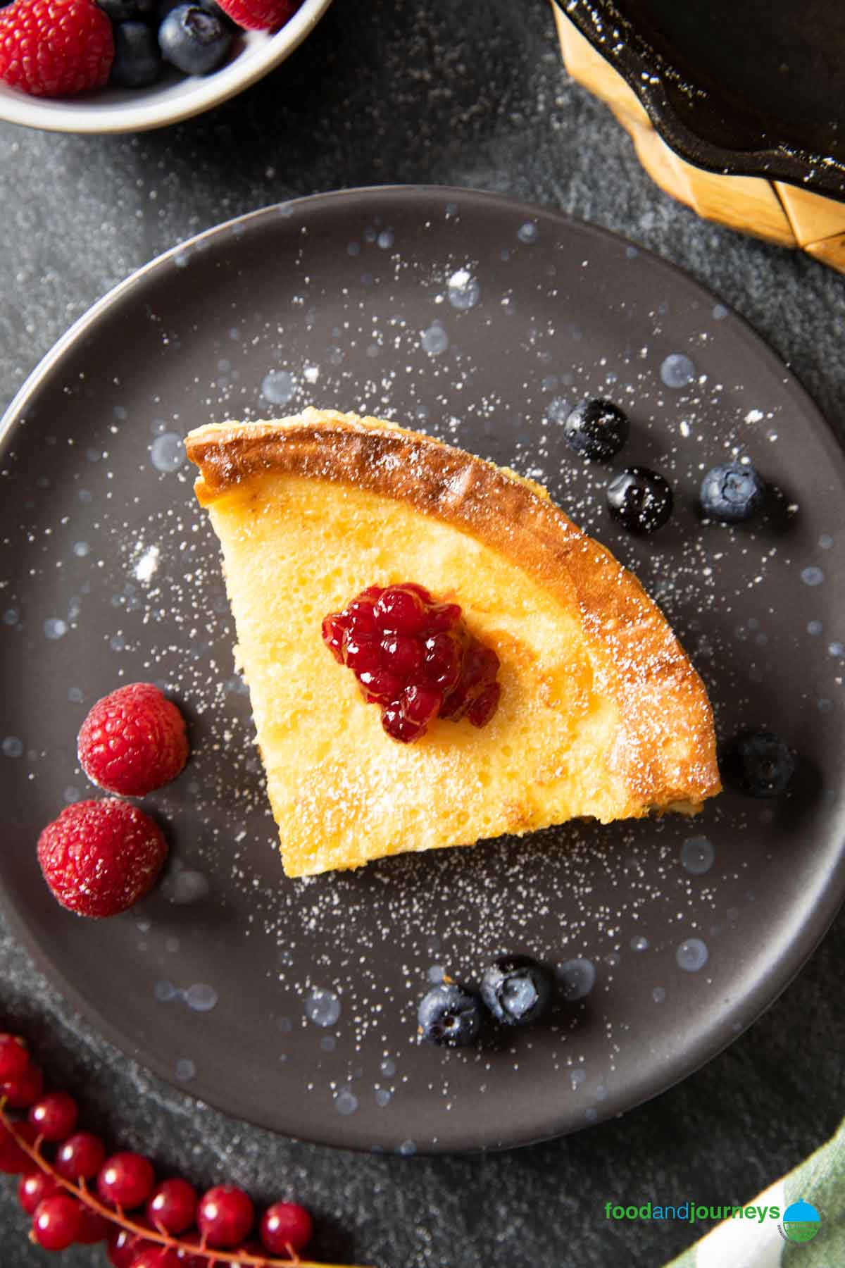An overhead shot of a serving of Finnish Oven-Baked Pancake, sprinkled with powdered sugar and a dollop of jam in the middle.