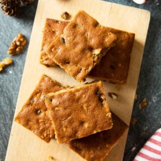 Overhead shot of slices of Date and Walnut Bars, served with a cup of coffee.