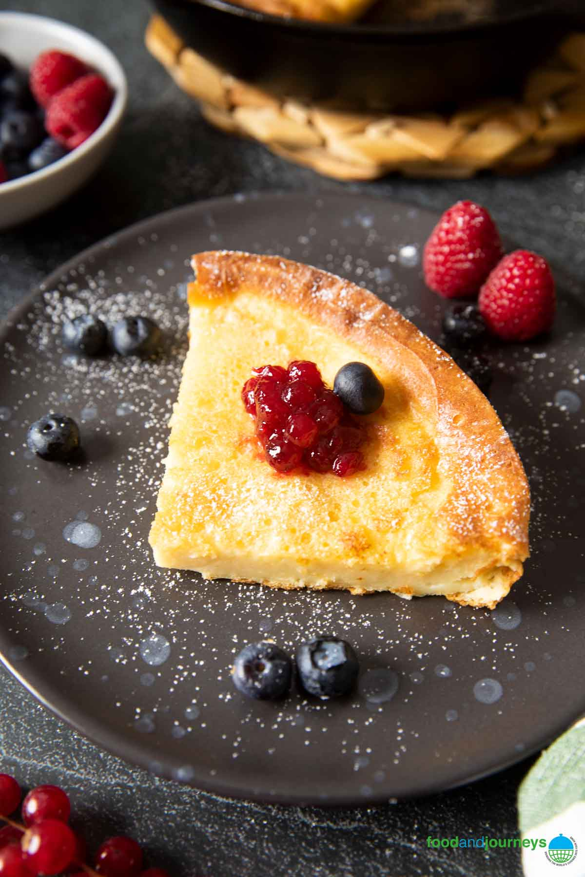 A closer shot of a serving of baked pancake, highlighting the texture inside the pancake, served with fresh fruits and jam.