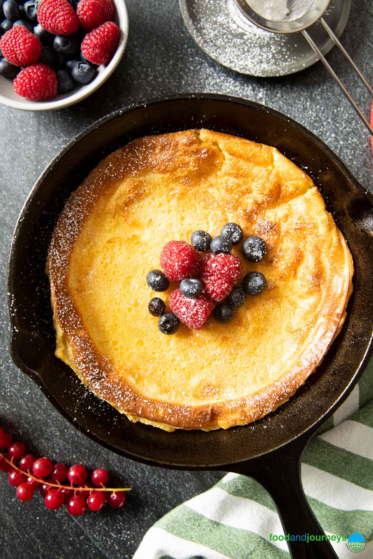 An overhead shot of Finnish Oven-Baked Pancake, straight out of the oven, sprinkled with powdered sugar and served with fresh berries.