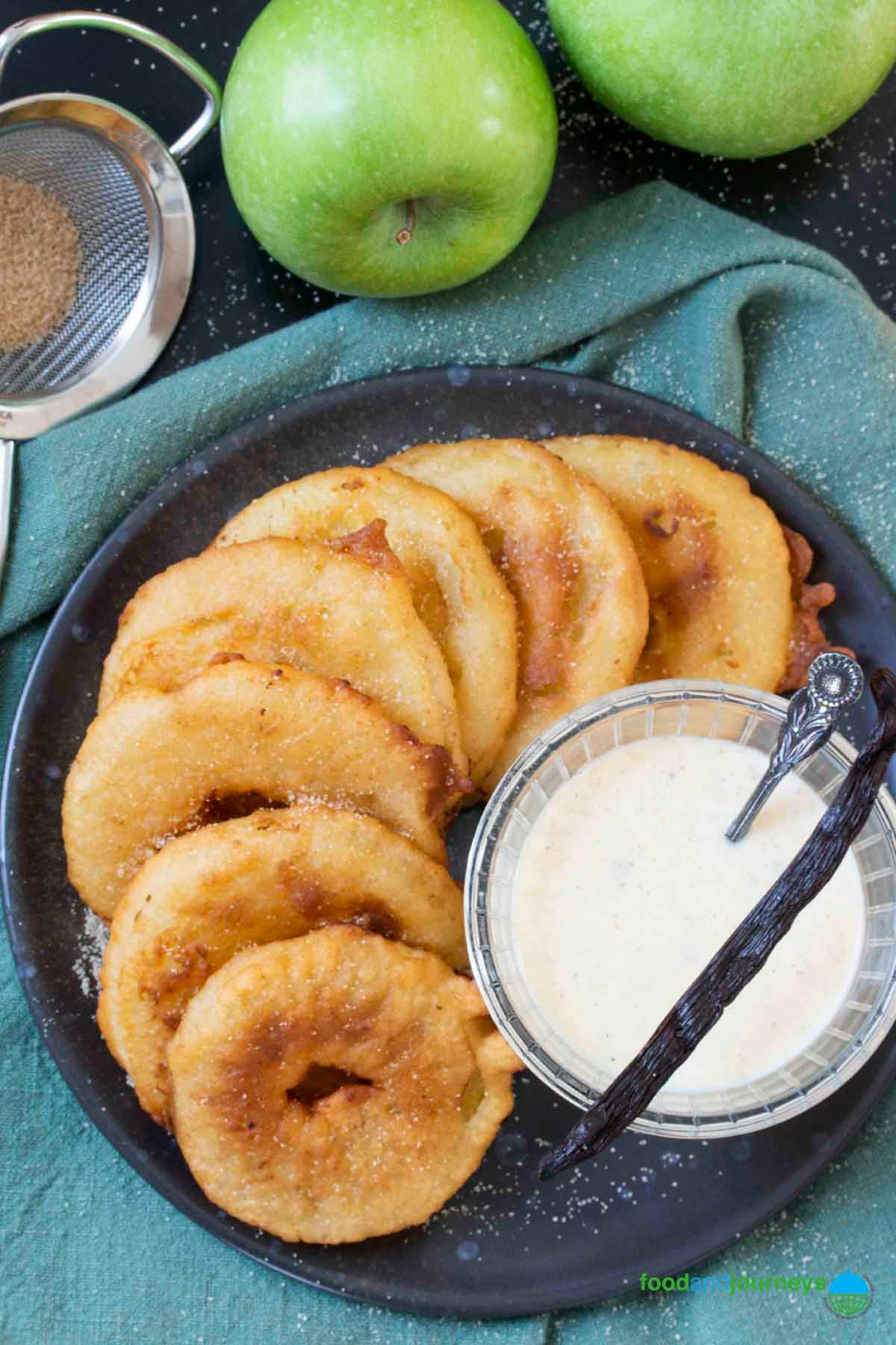 An overhead shot of a plate full of fried apples, served with vanilla sauce.