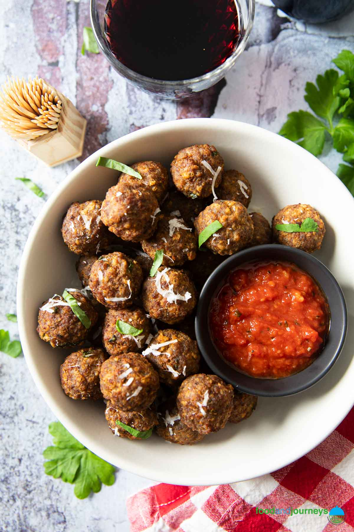 An overhead shot of a plate of mini meatballs served for appetizer, with some toothpicks and a glass of wine on the side.