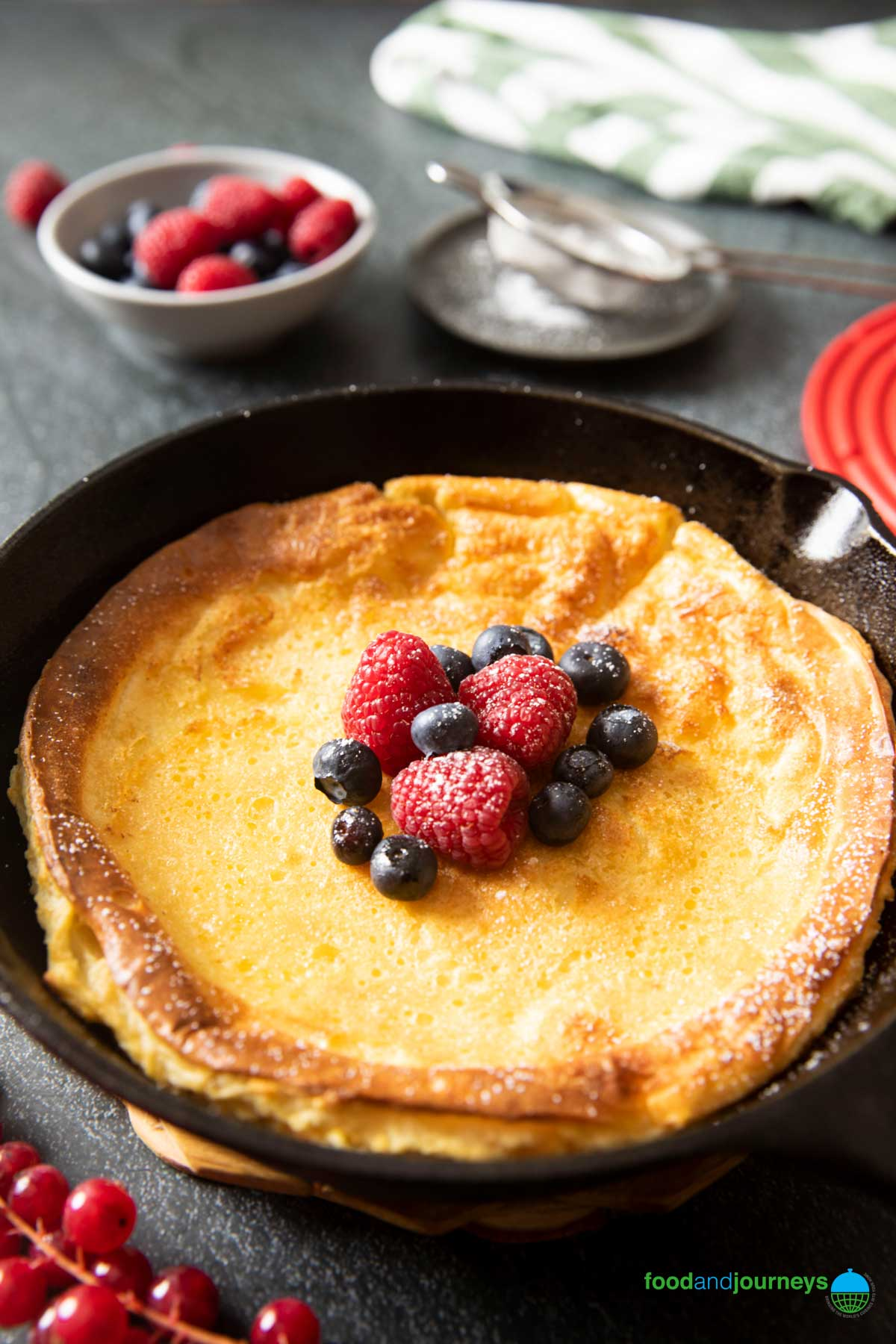 An image showing the side of an oven-baked pancake in a skillet, highlighting the thickness of the pancake, with fresh berries in the background.