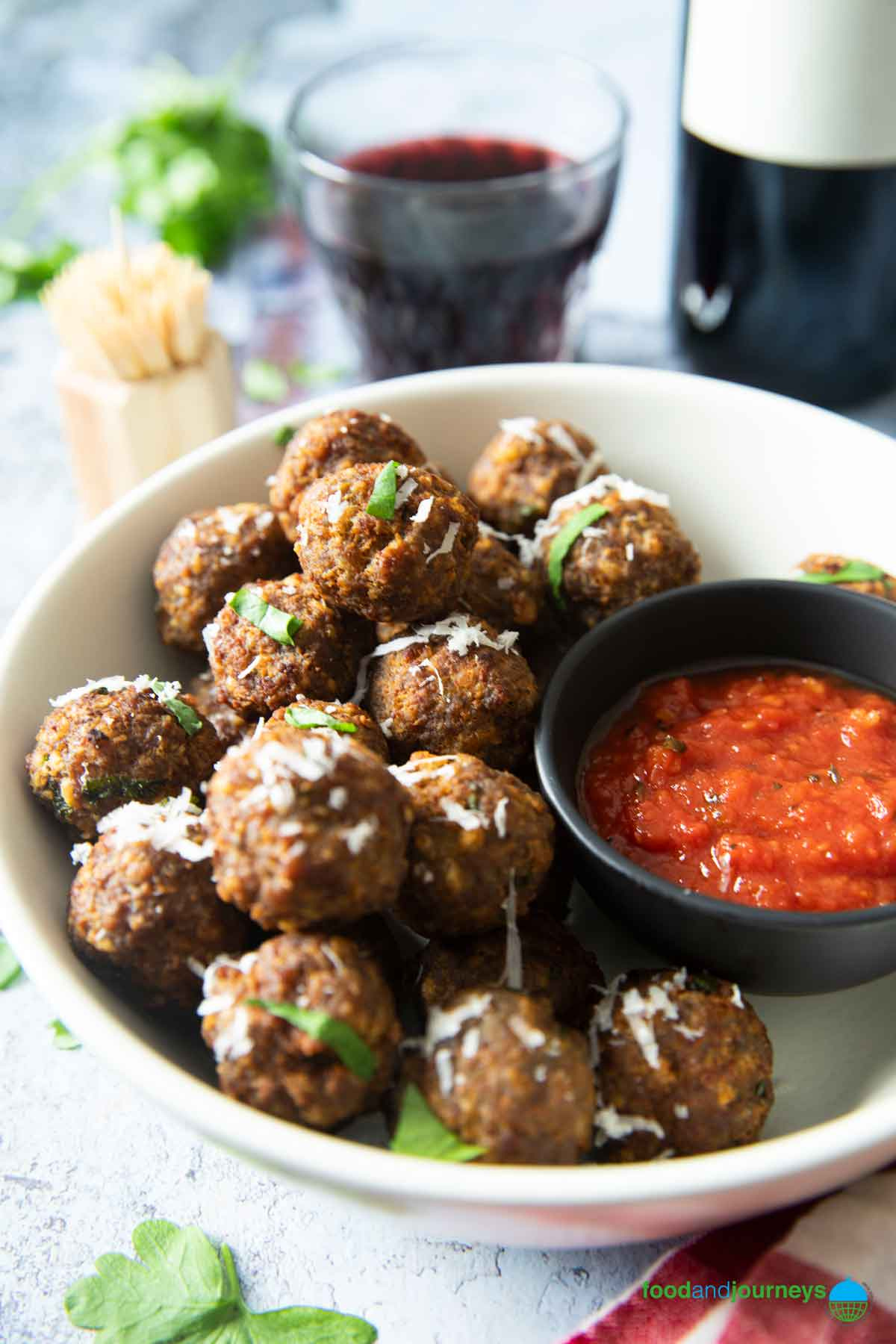 A closer shot of a plate of Italian meatballs, served with some marinara sauce, and a glass of wine.