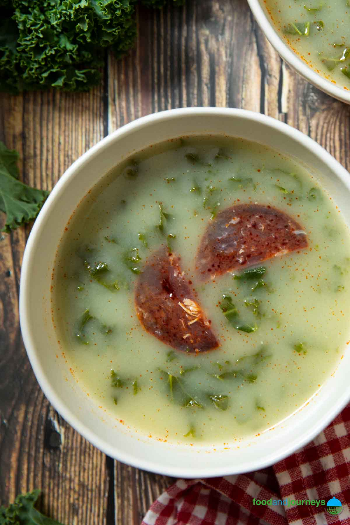 A serving of Portuguese Kale Soup, with slices of chorizo on top.