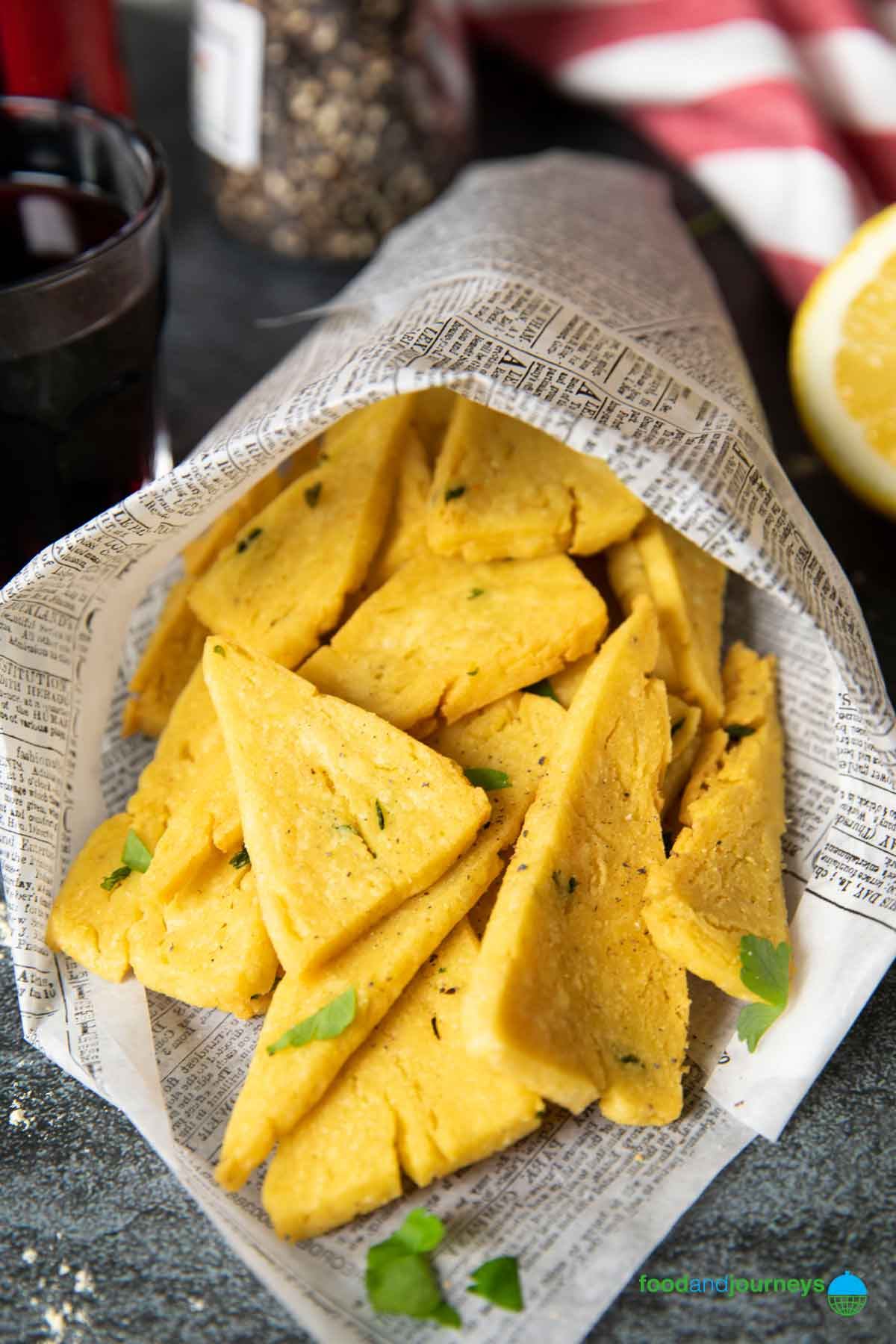 Panelle served in a paper cone, straight out of the fryer, garnish with ground pepper and fresh parsley.