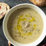 A bowl of Roasted Eggplant Soup, served with some slices of country bread.