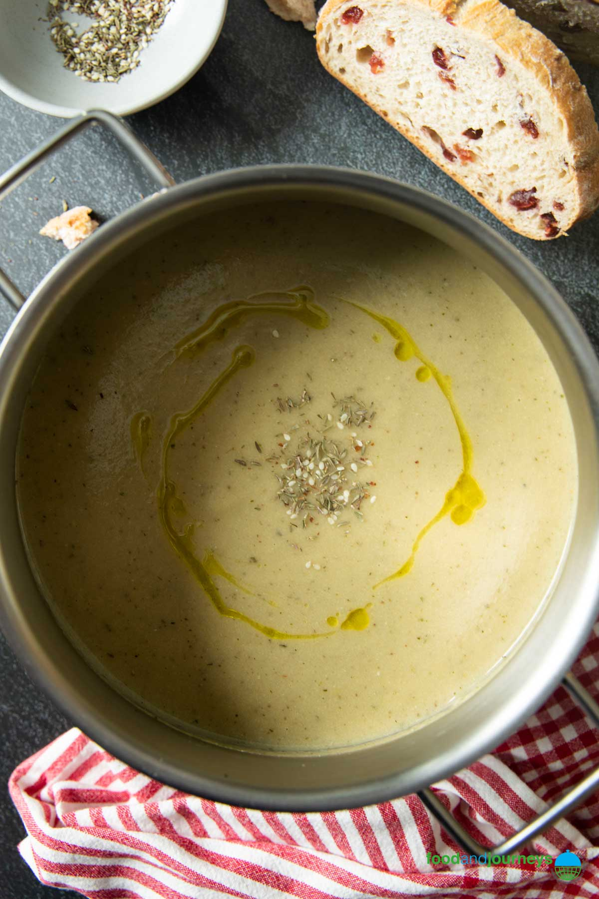 An overhead shot of a pan of Turkish-Style Roasted Eggplant Soup, served with some bread.