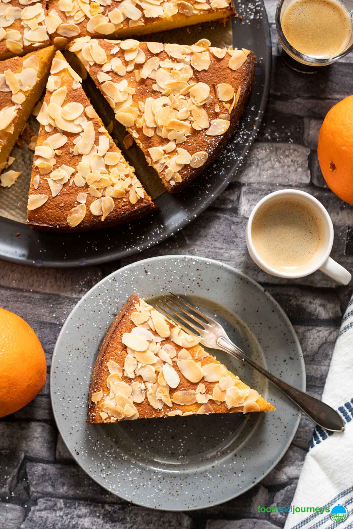 An overhead shot of a slice of flourless orange cake, served with a cup of espresso, with the rest of the cake on the side.