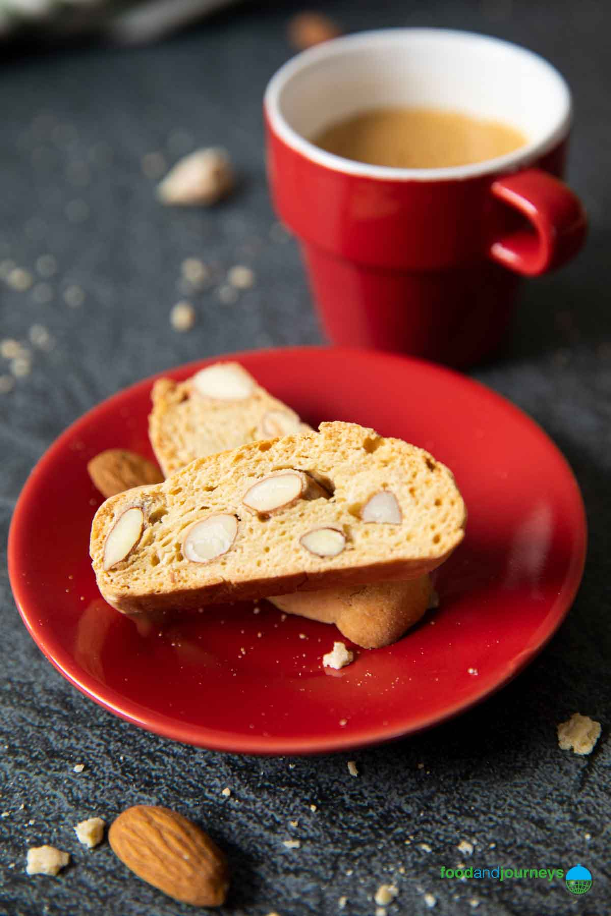 An image showing two Tuscan Almond Biscotti served with an espresso.