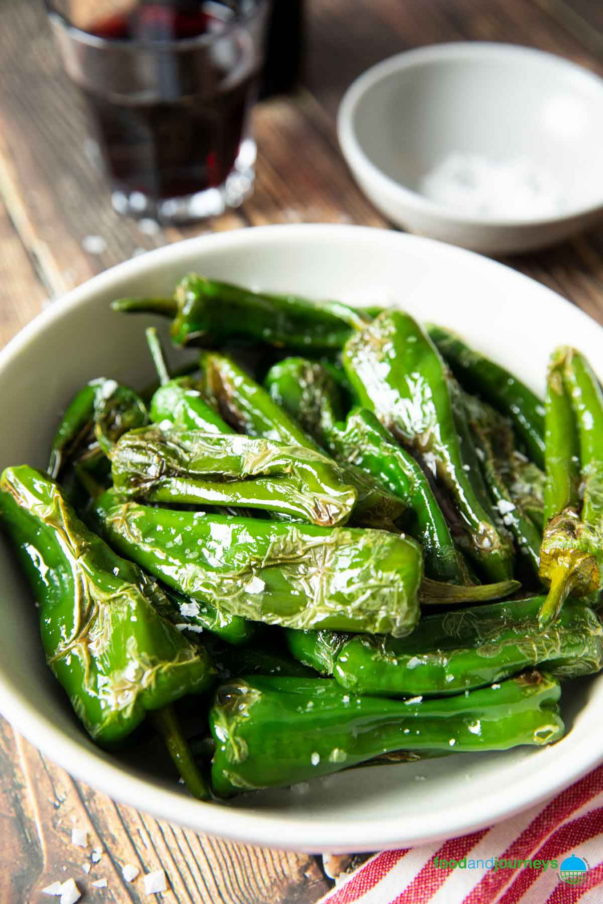 A closer shot of a serving of fried padron peppers, with sea salt on it.