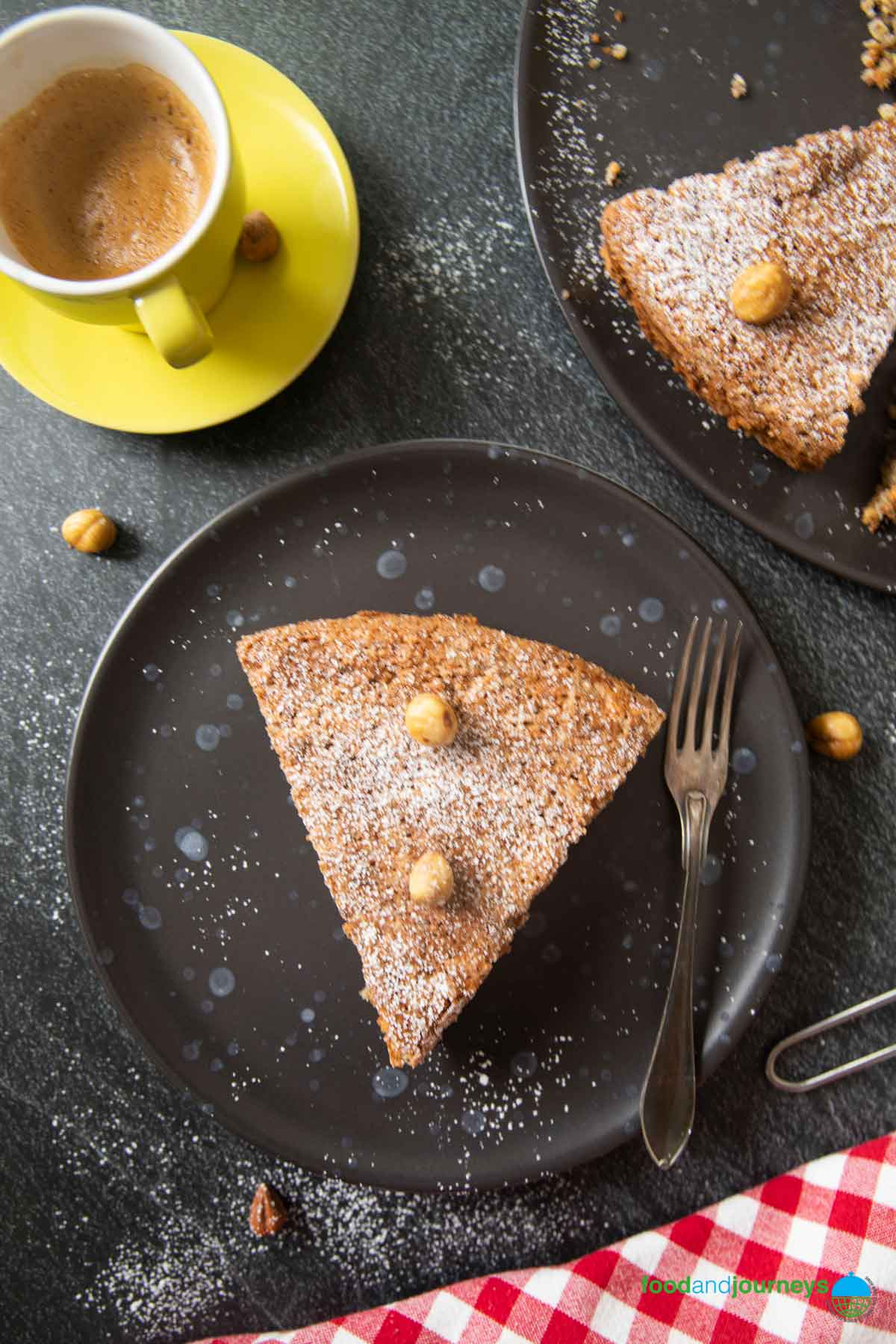 An overhead shot of a serving of hazelnut cake, with a cup of espresso on the side.