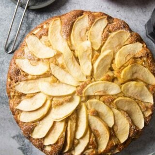 An overhead shot of a freshly baked Italian Apple Cake, with powdered sugar and fresh apples on the side.