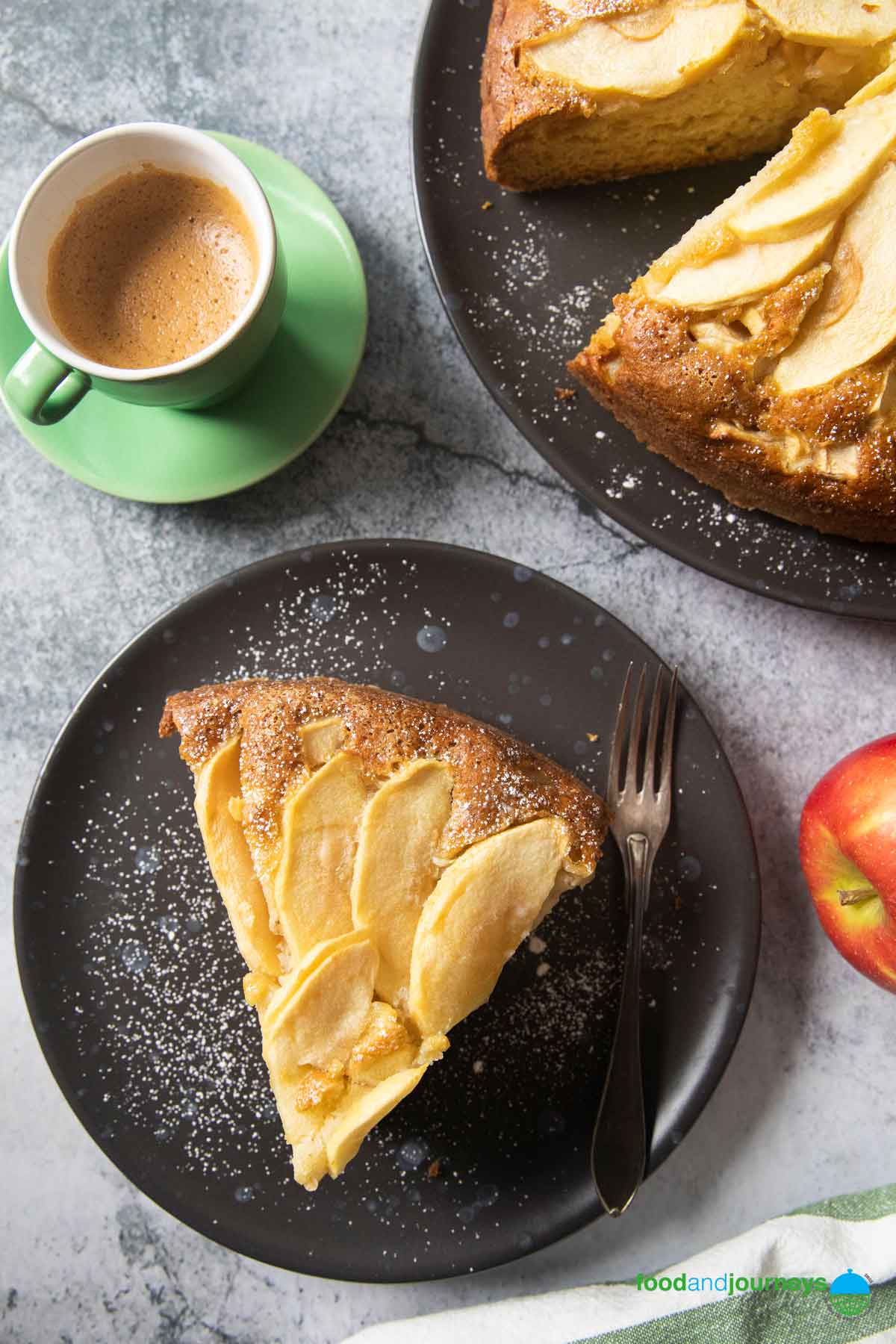 An overhead shot of a slice of rustic apple cake, served with espresso.