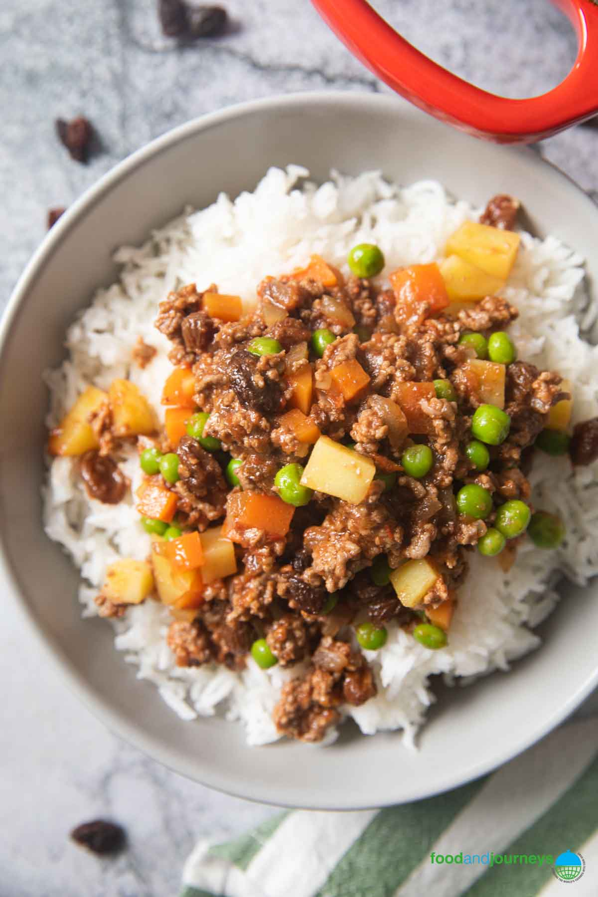 Beef picadillo served on top of steamed white rice, with some dried raisins on the counter.