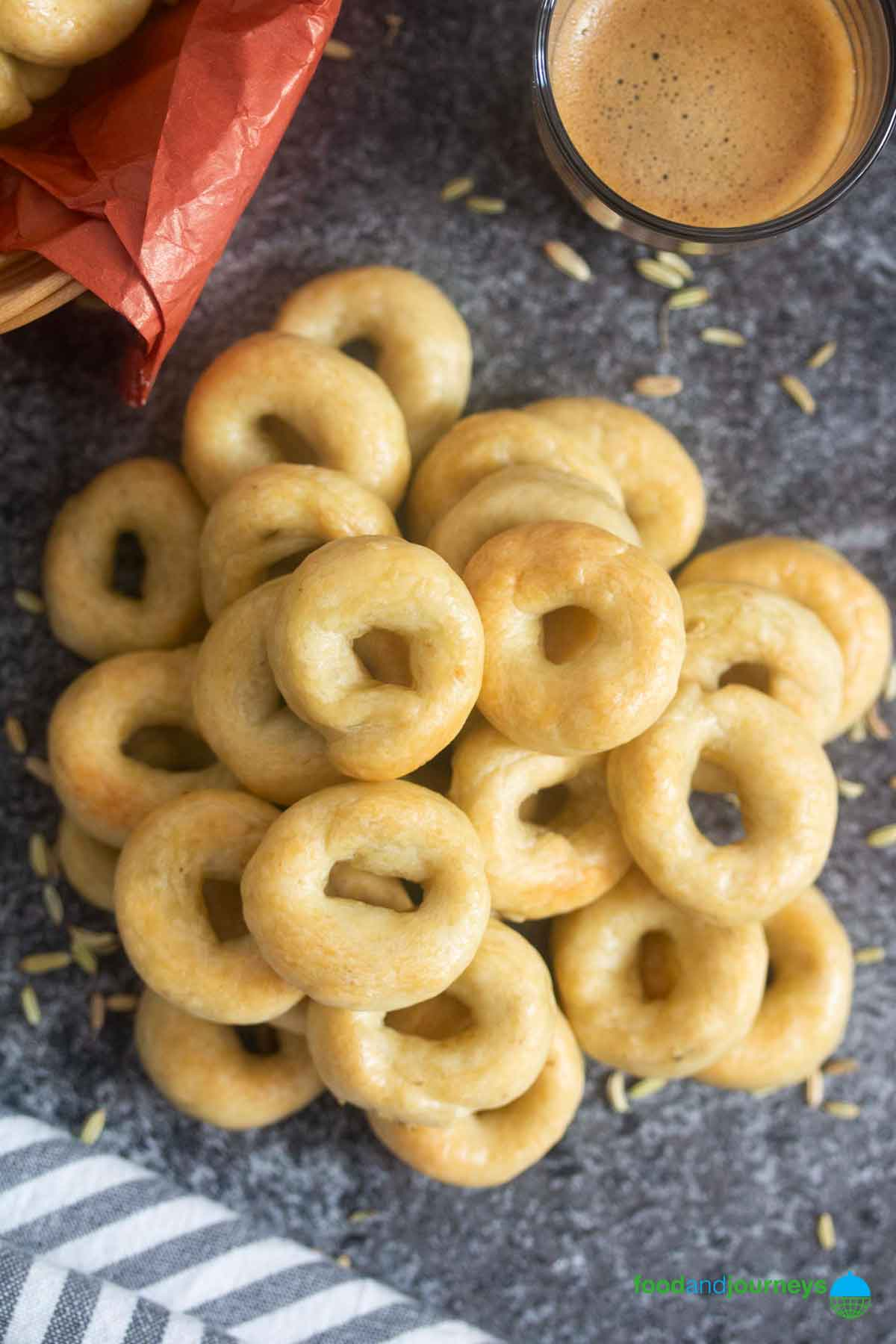 An overhead shot of a bunch of freshly baked taralli, served with a shot of espresso, with scaterred fennel seeds on the background.