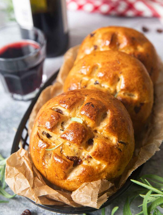 Three pieces of Italian Easter buns served with a glass of wine, and some fresh rosemary in the background.