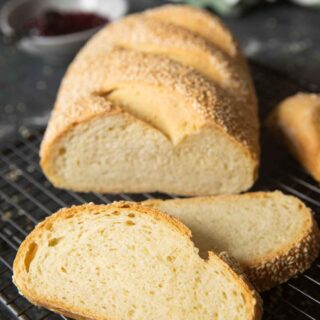 A loaf of semolina bread on a cooling rack, with a couple of slices ready for serving.