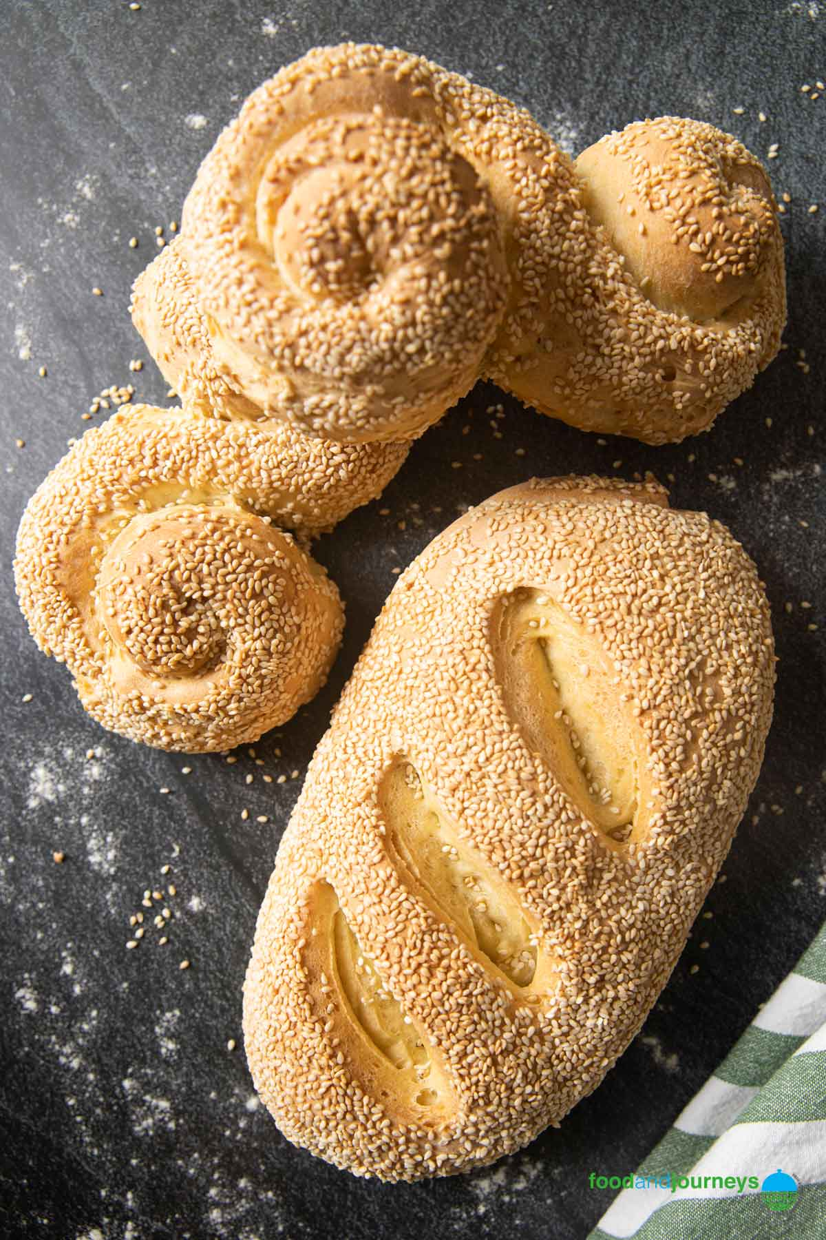 An image showing freshly baked Pane Siciliano, one a loaf and two in their traditional shapes.