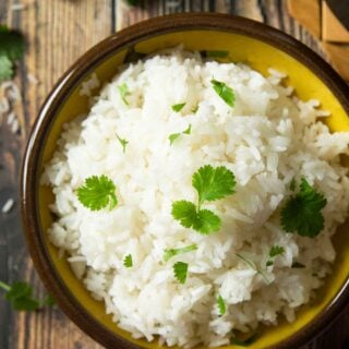 An overhead shot of a bowl of coconut rice, garnished with coriander, and ready for serving