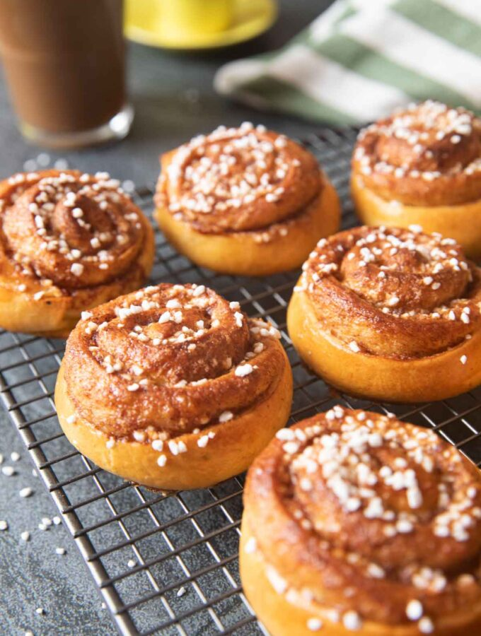 A closer shot of kanelbullar on a cooling rack, highlighting the filling of the buns.