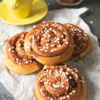 A pile of kanelbullar served with a cup of espresso and a tall glass of coffee.