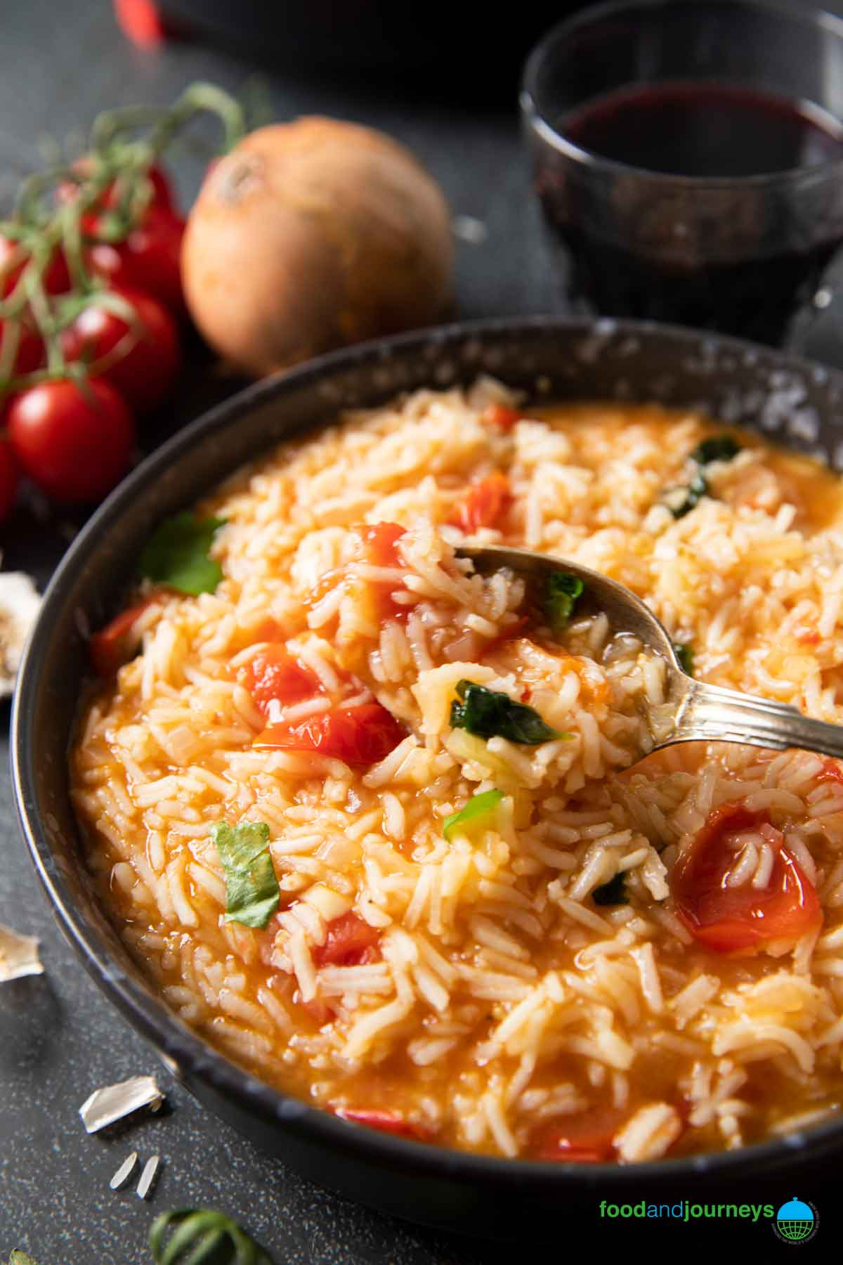 A closer shot of a serving of tomato rice, with a spoon showing the texture of the rice.