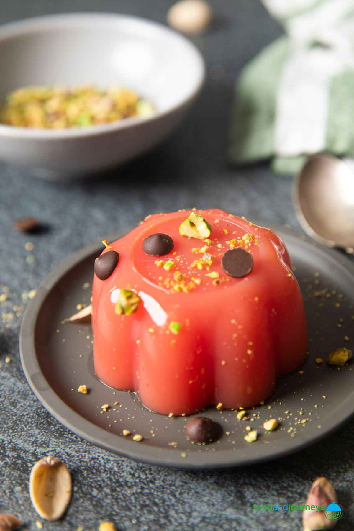 A serving of Sicilian watermelon jelly with pistachios in the background.