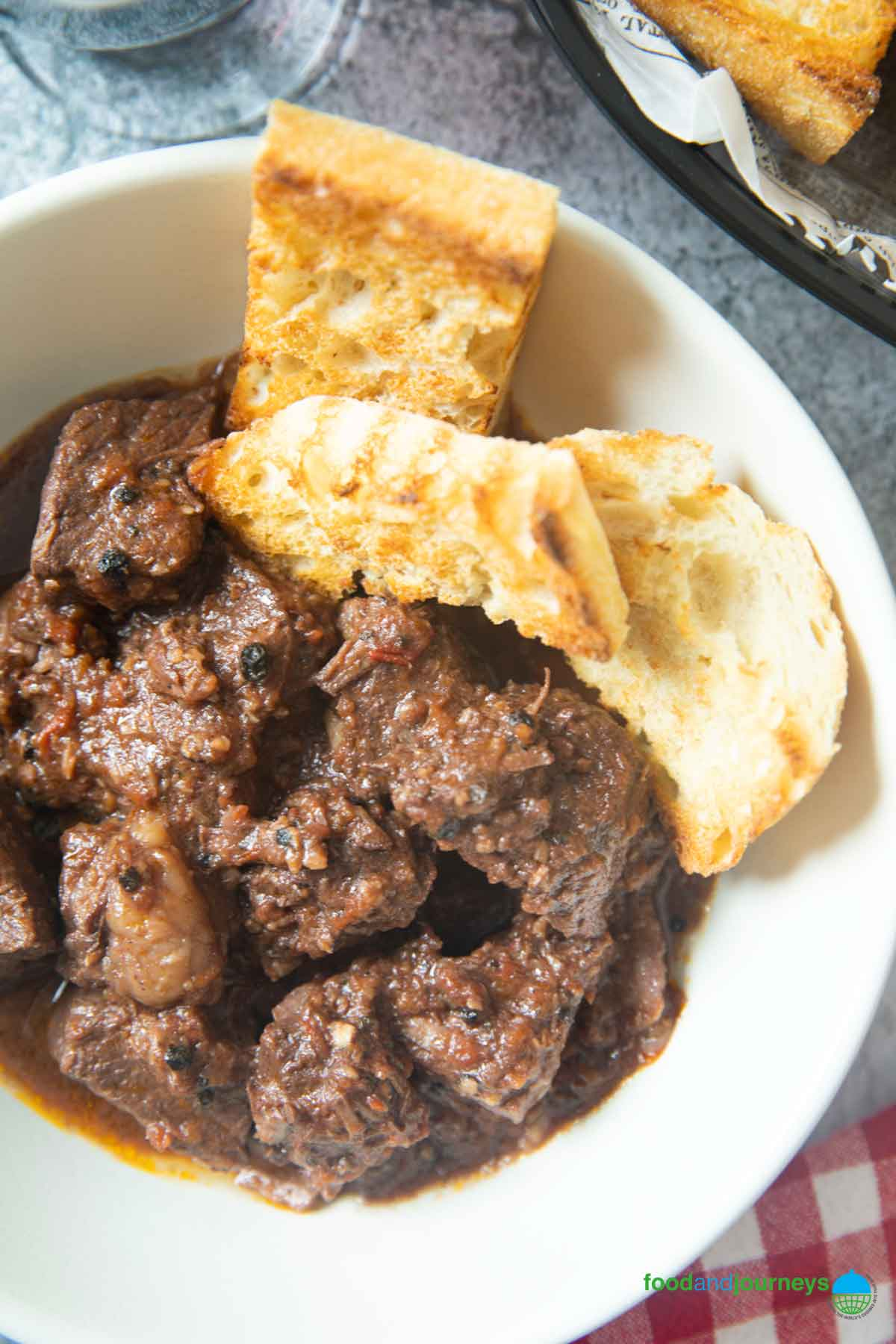 A closer shot of peposo, highlighting the peppercorns and the sauce coating the chunks of beef.