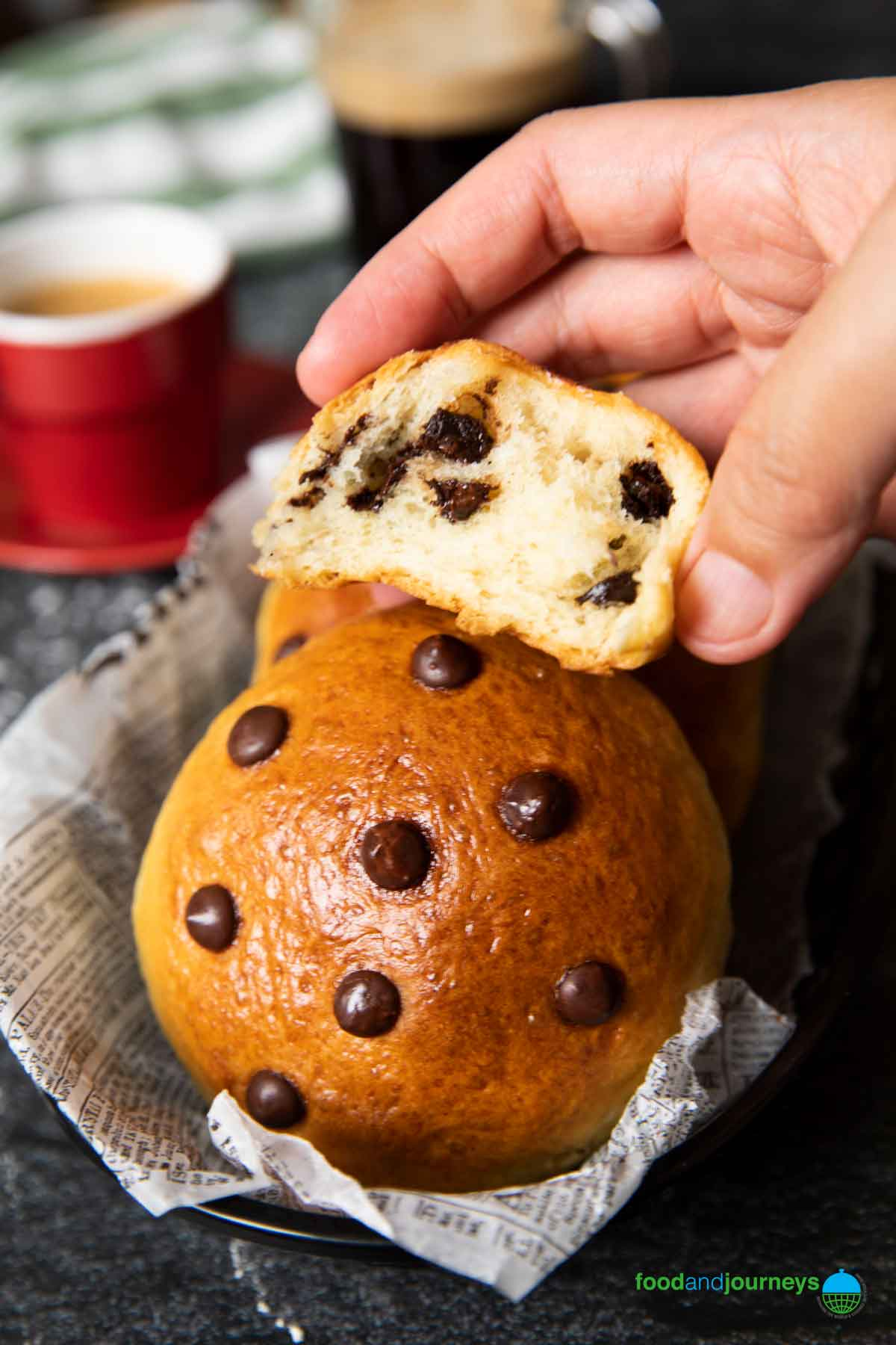 A shot of a half eaten chocolate bun, highlighting the texture of the roll.