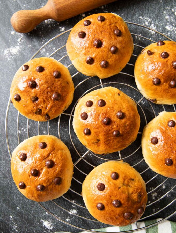 An overhead shot of freshly baked German chocolate buns on a cooling rack, with a rolling pin next to it.